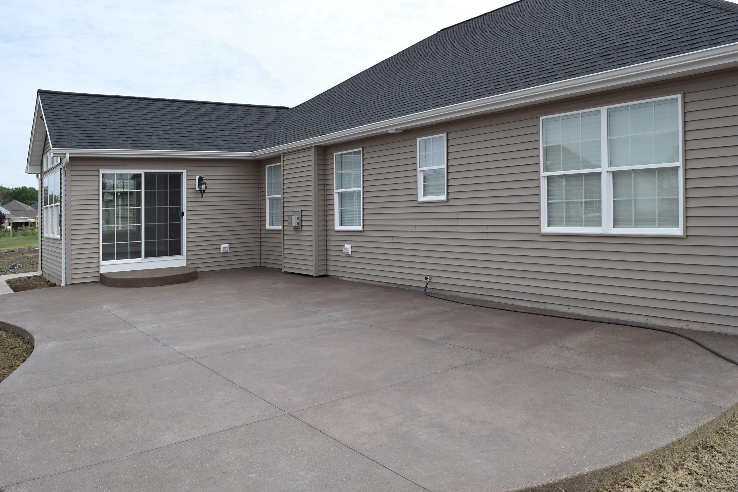 This is an image of a concrete patio in the back of a house.
