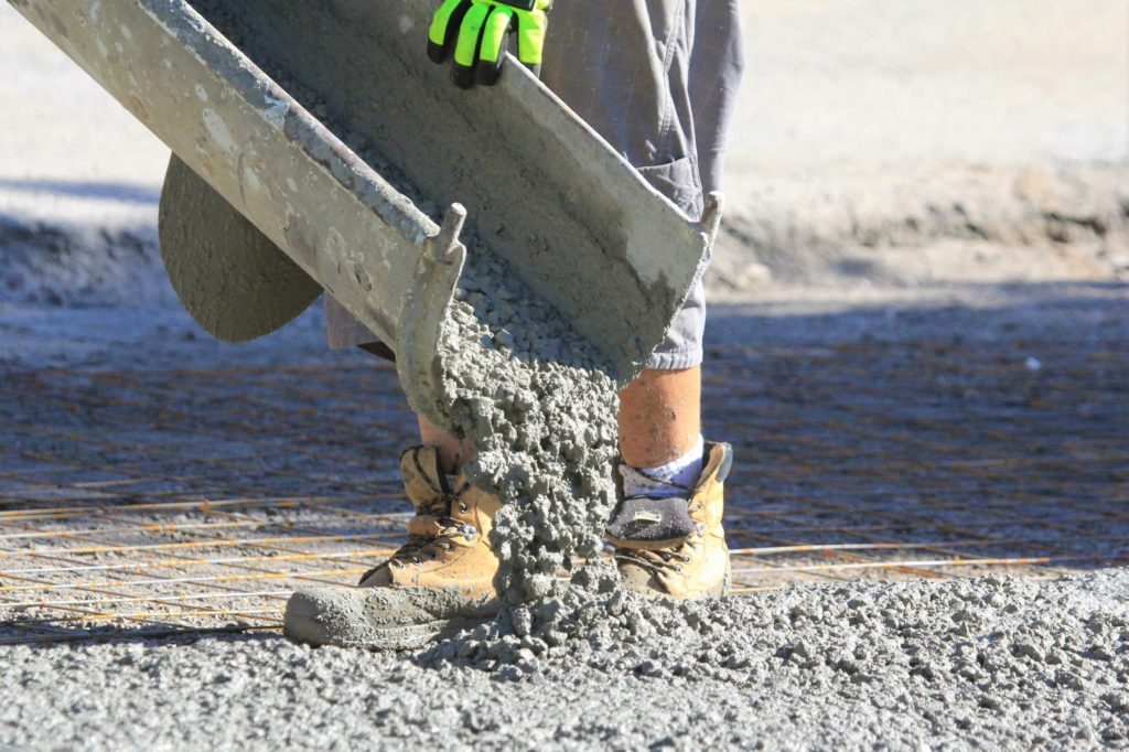 This is an image of a contractor pouring concrete onto a building foundation.