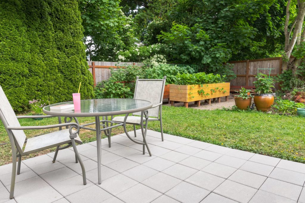 This is an image of a backyard concrete patio with stamped tile design.