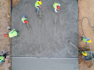 This is an image of a team of contractors distributing cement for a concrete driveway.