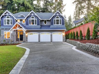 This is an image of a beautiful blue house with a concrete driveway.